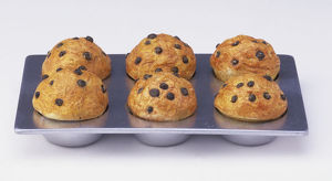 Tray of six baked muffins topped with raisins, high angle view.