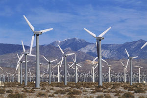 USA, California, Coachella Valley, field of wind turbines against mountain backdrop.