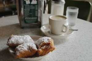 USA, Louisiana, New Orleans, Cafe du Monde, cup of espresso coffee next to icing