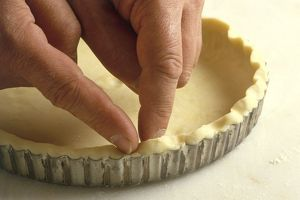 Using finger to flute pastry around edges of tart tin, close-up