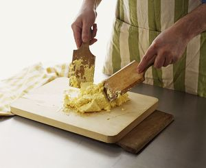 Using pair of wooden paddles to shape butter on chopping boards