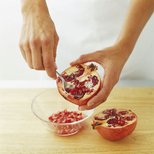 Using spoon to remove pomegranate seeds