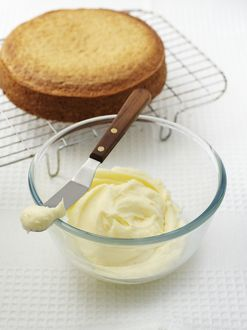 Vanilla buttercream icing in glass bowl and on cake spatula, cake on cooling rack nearby
