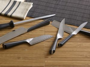 Various knives and sharpener, on bamboo place mats