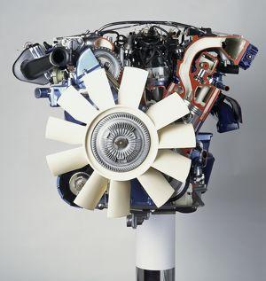 Front view of a V12 petrol engine with white fan at the front.