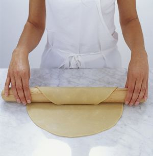 Woman draping pastry over rolling pin
