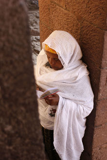 universal images group/editorial religion woman/woman reading scriptures outside bet medhane alem