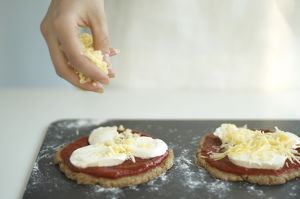 Woman's hand putting grated cheddar cheese on wholemeal mini pizzas