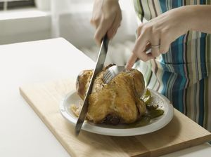 Woman's hands carving roast chicken, close-up