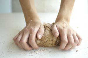 Woman's hands kneading whole wheat pizza dough