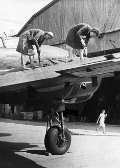 Two women working on the metal covering of a wing of a soviet military plane during world war 2