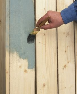 Wooden planks being painted grey with a brush.