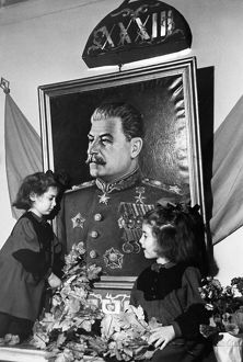 Two young girls at a kindergarten in the sverdlov district of moscow adorning a portrait