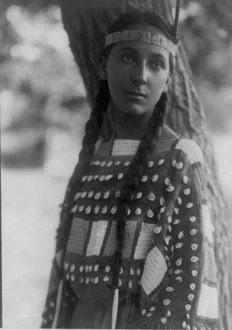 Young Native American woman, half-length, portrait, standing, facing front, 1907