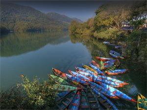 Colourful hire boats tied up on the shoreline of Lake Pokhara, Nepal.