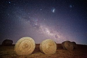 Milky way and magellanic clouds over hay bales