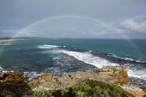 Rainbow over coast and ocean. Australia.