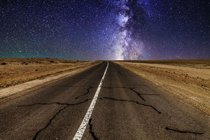 Road in the desert at night with the Milky Way