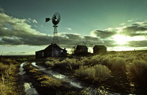 Abandoned homestead with windmill at sunrise