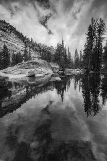 Black and white image of granite outcropping with boulders by lake, Yosemite National Park