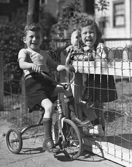 Boy on tricycle w/ girl