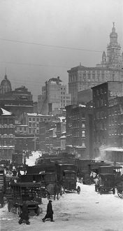 circa 1925: A view of a group of automobiles and wagons parked in the snow at the