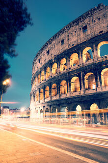 Colosseum at night with light trails from cars