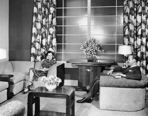 Couple sitting in living room reading