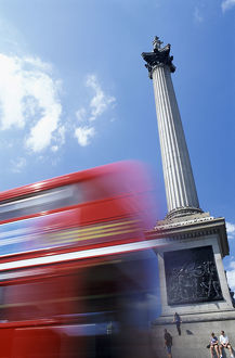 Double Decker Bus Driving past Nelson's Column on Trafalgar Square, Tourists Sitting on Steps