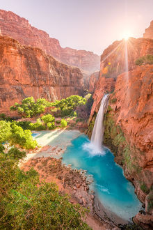 Havasu Falls in Arizona plunges in turquoise waters as the sun rises above the cliffside