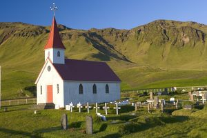 Iceland, church and graveyard in mountainous landscape