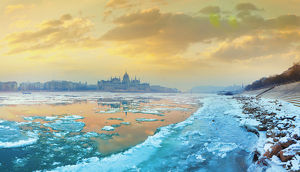The icy Danube river and the Parliament of Hungary in Budapest at dawn in the winter