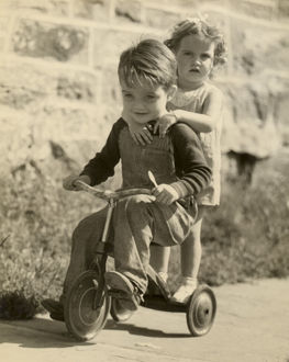 Little boy giving little girl ride on tricycle