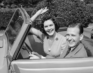 Man driving car and woman waving