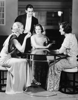 Man talking with three women in evening wear