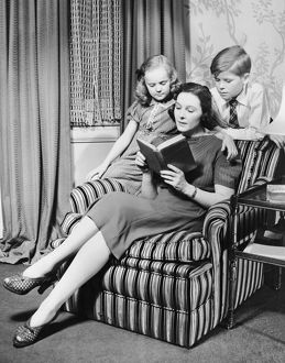 Mother reading to daughter & son