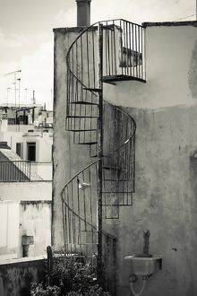 Old cast iron spiral staircase accessing a rooftop terrace in Otranto, Apulia, Italy