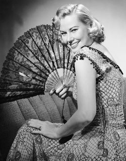 Portrait of blonde woman holding fan