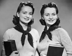 Portrait of teenaged twin girls holding books