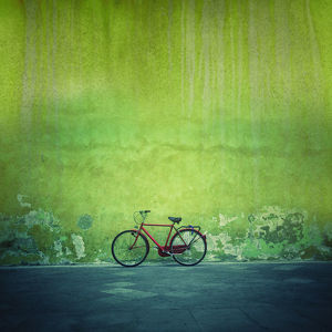 Red vintage bike against a green flaking plaster wall