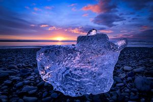 Sunrise over ice at black beach of JA¶kulsA¡rlA³n glacier lagoon