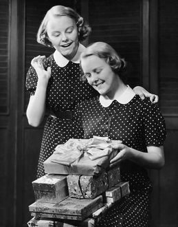 Twin teenage girls w/ wrapped gifts