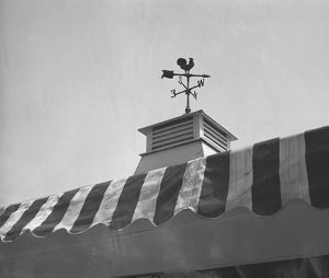 Weather vane on roof tower, (B&W), low angle view
