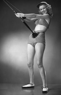 Woman in beachwear holding fishing rod