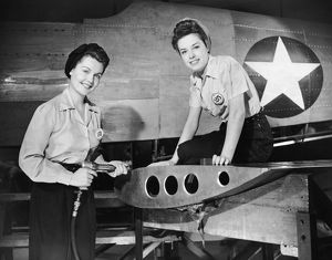 Two women working on airplane