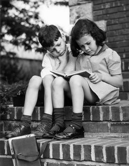 Young boy & girl reading a book outdoors
