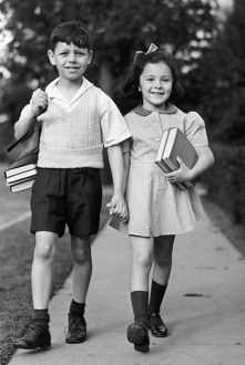 Young girl & boy walking to school w/ books