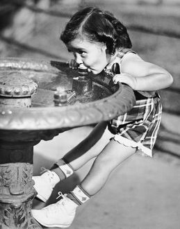 Young girl drinking from water fountain