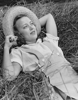 Young woman laying in hay thinking
