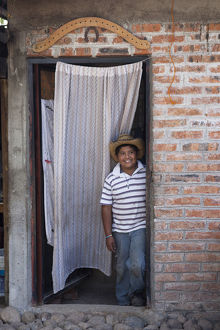 Antonio, 11 years old, in the doorway of his house